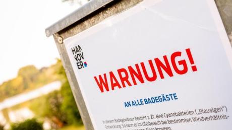 Ein Hinweisschild warnt Badegäste vor Blaualgen. Sommerliche Temperaturen können Ursache eines starken Wachstums sein.