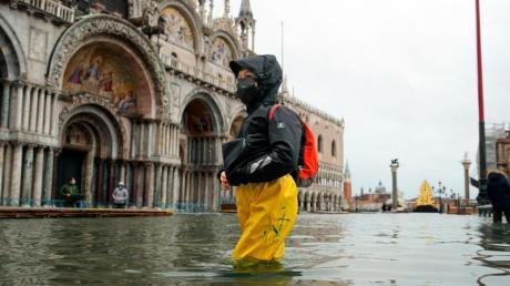 Eine Passantin bahnt sich ihren Weg durch den überfluteten Markusplatz. Starke Regenfälle haben in Venedig Teile der Stadt überflutet.
