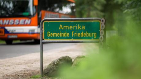 Ein Bus fährt an dem Ortsschild Amerika vorbei, einem Ortsteil von Friedeburg.