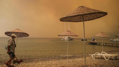 Ein Mann mit Hund am Strand in der Ferienregion Bodrum: In Teilen der Türkei toben heftige Brände.