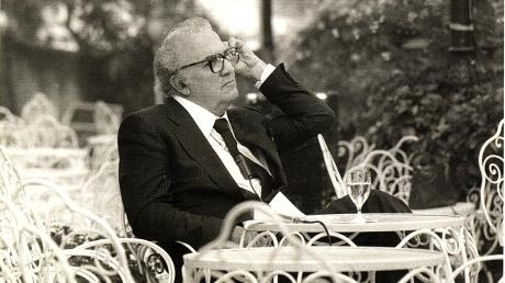 Federico Fellini im Garten des Grand Hotels in Rimini in Denkerpose.