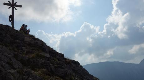 Das Gipfelkreuz der Scheinbergspitze in der Abenddämmerung.