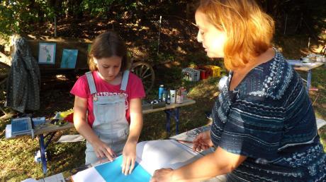 Künstlerin Nickel Altmann (rechts) zeigte Kindern wie Katharina, wie Fadenbilder gefertigt werden. <b>Foto: Karin Marz</b>