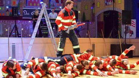 """Mit dieser Rollakrobatik erreichte die """"brandheiße"""" Chorographie der Schwabmünchner Feuerwehr ihren ersten Höhepunkt. Elfengleich, in grazilem Sprung, verabschiedeten sich die Männer der Feuerwehr später von den tobenden Damen."""