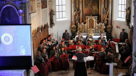 In seinem Passionskonzert vereinte der Musikverein die meditative Betrachtung des Misereor-Hungertuchs (links auf der Leinwand) mit passend dazu ausgewählter sakraler und weltlicher Blasmusik.