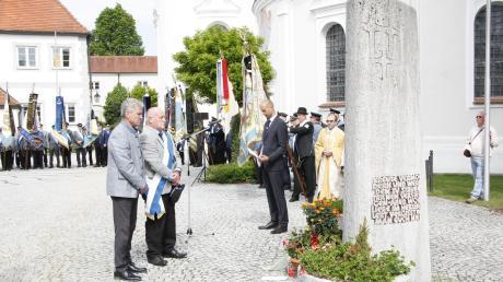 Bürgermeister Rudolf Schneider (links) und Rudi Henkel legten eine Blumenschale zum Gedenken der Opfer am Kriegerdenkmal nieder. Rechts von ihnen Marco Meyer und Pfarrer Thomas Demel (links). Die Fahnenabordnungen bildeten eine prächtige Kulisse für den Gottesdienst, den Pfarrer Thomas Demel und Diakon Bruder Kornelius feierten (rechts).
