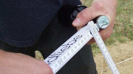 Mithilfe eines Werkzeugs, wie hier einem Meterstab, wird die Bierkapsel so weit wie möglich katapultiert.