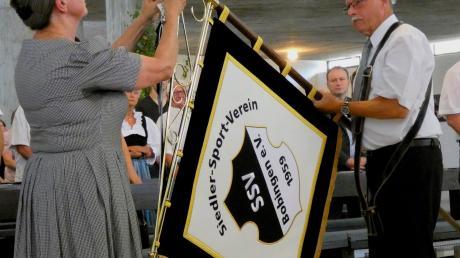 Jutta Miethig und Franz Rampp befestigen das Trauerband an der frisch geweihten Standarte des SSV Bobingen.  Foto: Elmar Knöchel