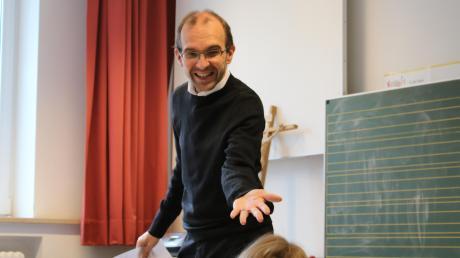 Als Lehrer zeigt sich Pfarrer Thomas Demel von seiner fröhlichen Seite und scherzt mit den Schülern in Untermeitingen.