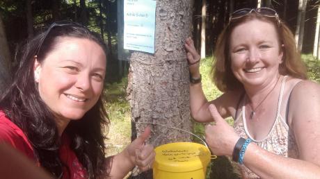 Simone Höfle (links) und Wiltrud Zureck haben eine Station der Schnitzeljagd im Wald erreicht.