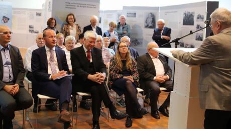 """Bei der Eröffnung der Wanderausstellung """"Erzwungene Wege"""" waren (von links) Andreas Jäckel, Martin Sailer, Christian Knauer, Annemarie Probst, Friedrich Behrend anwesend. Im Hintergrund befinden sich außerdem einige Zeitzeugen, die auch von Kurt Aue (am Rednerpult) begrüßt wurden."""