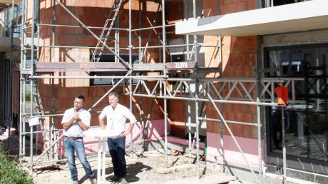 Josef Egger (rechts) von der Architekturagentur in Bobingen und Oberottmarshausens Bürgermeister Gerhard Mößner vor dem Rohbau der Paarhäuser.