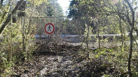 Wo einst eine Brücke über den Lochbach führte, stehen Spaziergänger heute vor einem Absperrgitter. Viele Königsbrunner ärgern sich, weil sie zum Mandichosee nun einen größeren Umweg in Kauf nehmen müssen.