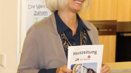 Liane Uhde stellte die Hauszeitung als Festschrift vor. Schwabmünchens Bürgermeister Lorenz Müller servierte der ältesten und langjährigsten Bewohnerin des Haus Raphael, Maria Eichner, Weißwürste beim Brunch des Seniorenzentrums.