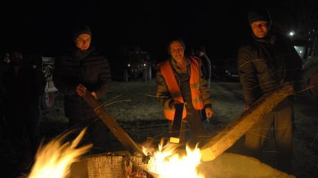 Die Landwirte Matthias Port, Manfred Pfitzmayr und Georg Büschl schüren das Mahnfeuer.