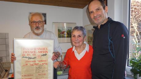 Heinrich Heinemann (links) und Ehefrau Lore trennen sich von Erinnerungen und geben unter anderem das Plakat sowie ein Stück Original-Stacheldraht des Grenzzaunes zwischen Ungarn und Österreich an Harald Adam-Götz vom Museum in Ulm.