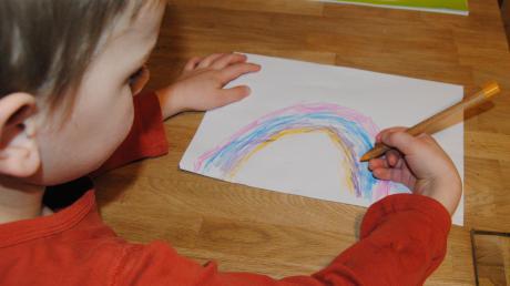 Auch Paulus malt einen Regenbogen und hängt ihn für seine Freunde ins Fenster.