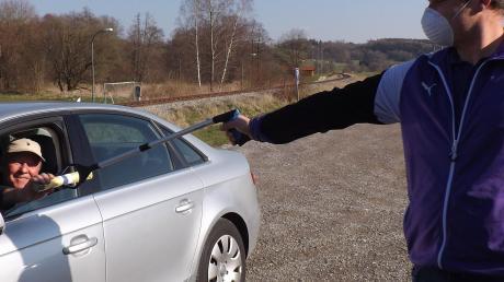 Christoph Endres (rechts) vom TSV Walkertshofen übergibt mittels einer Greifzange eine Rolle gelber Säcke an einen Autofahrer.