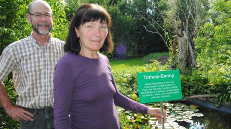 Eine Totholzpyramide ist im Garten von Veronika Schwarzenberger entstanden. Die Infotafel in ihrer Hand werden sie und Peter Roth aber im Singoldpark anbringen, um dort die Besucher zu informieren.