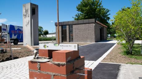 Die entstehenden Mauerpfosten am Osteingang des Lagerlechfelder Friedhofs lassen die neue Toranlage erahnen, der Platz vor dem Gebäude wurde von der düsteren Pergola befreit.