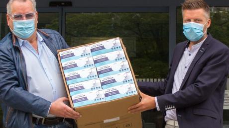 Roland Stark (links), Inhaber der Wehringer Firma Winsport, übergab den ersten Karton mit MSN-Masken persönlich an Klinikvorstand Martin Gösele.
