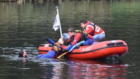 """Junge Rettungsschwimmer der Schwabmünchner Wasserwacht retten eine Person mit einem sogenannten """"Spineboard"""" aus der Wertach."""