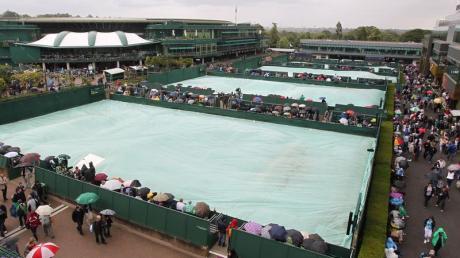 Die Zuschauer versteckten sich unter Regenschirmen, die Plätze wurden abgedeckt: Es regnete mal wieder in Wimledon.