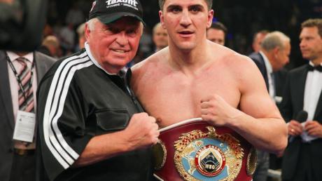 Marco Huck (r) posiert mit Trainer Ulli Wegner nach dem Kampf.