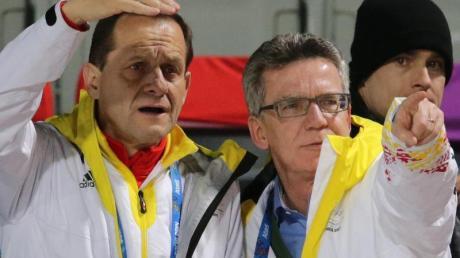 Alfons Hörmann (l) und Thomas de Maiziere schauen beim Skispringen zu.