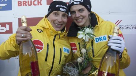 Anja Schneiderheinze (l) und Annika Drazek feiern den WM-Titel mit Champagner.