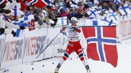Die Norwegerin Marit Björgen nimmt sich als Schlussläuferin der Staffel auf den letztem Metern vor dem Ziel eine Fahne.