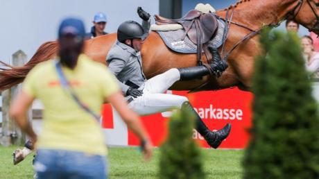 Der Reiter Philipp Weishaupt fällt von seinem Pferd Che Fantastica herab. Foto: Rolf Vennenbernd/Archivbild