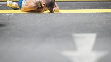 Der italienische Geher Michele Antonelli liegt im Ziel erschöpft auf dem Asphalt. Foto: Oliver Weiken
