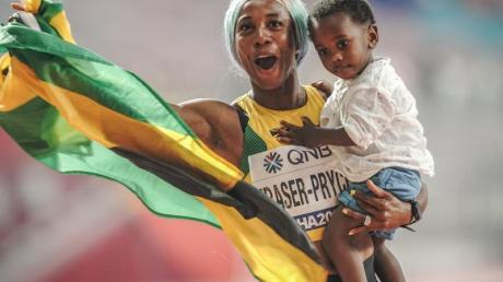 Sprint-Weltmeisterin Shelly-Ann Fraser-Pryce feiert ihren Erfolg mit ihrem Sohn Zyon auf dem Arm.