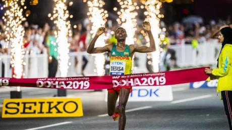 Lelisa Desisa aus Äthiopien überquert die Ziellinie und gewinnt den Marathon. Foto: Jean-Christophe Bott/KEYSTONE/dpa
