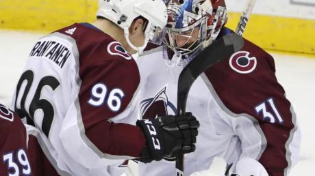 Mikko Rantanen (l) und Goalie Philipp Grubauer von Colorado Avalanche jubeln über den Sieg im Spiel gegen New Jersey.
