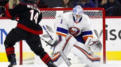 Justin Williams (l) von den Carolina Hurricanes in Aktion gegen Goalie Thomas Greiss von den New York Islanders.