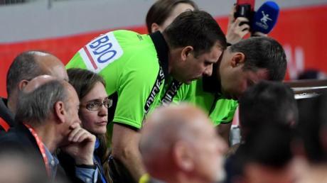 Zwei Schiedsrichter schauen beim Handball auf einen Bildschirm beim Videobeweis.