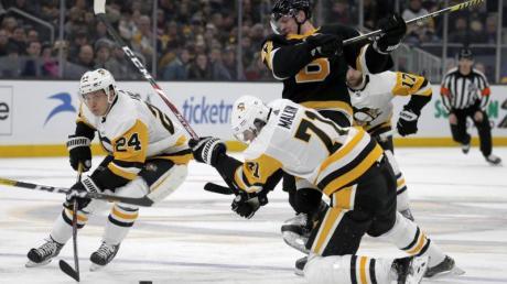 Dominik Kahun (l) von den Pittsburgh Penguins und sein Teamkollege Evgeni Malkin (vorn/71) in Aktion gegen Torey Krug (M) von den Boston Bruins.