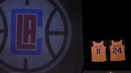 Trikots mit Kobe Bryants Nummern 8 und 24 sind bei einem Spiel neben dem Logo der LA Clippers aufgehängt.