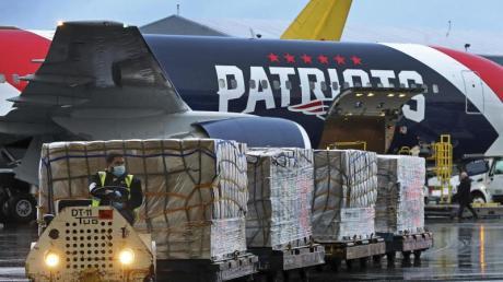 Paletten mit Atemschutzmasken werden aus dem Flugzeug der New England Patriots entladen.