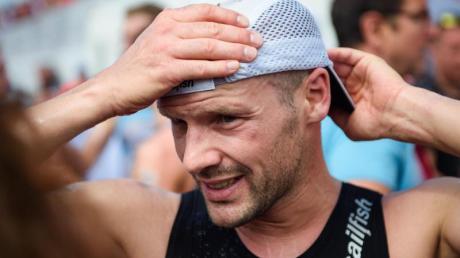 Patrick Lange, zweimaliger Sieger des Ironman Hawaii, rückt nach dem Zieleinlauf seine Mütze zurecht.