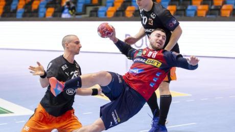 Jannik Kohlbacher (M) von den Rhein-Neckar Löwen setzt sich gegen die Schaffhausener Lukas Herburger (l) und Donat Bartok (r) durch.