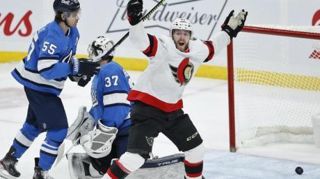 Chris Tierney (l) von den Ottawa Senators feiert den Siegtreffer von Brady Tkachuk (nicht im Bild) gegen Winnipeg Jets-Torwart Connor Hellebuyck (M) und Mark Scheifele (l).