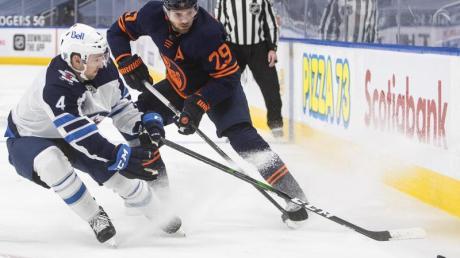 Leon Draisaitl (r) von den Edmonton Oilers in Aktion gegen Neal Pionk von den Winnipeg Jets.