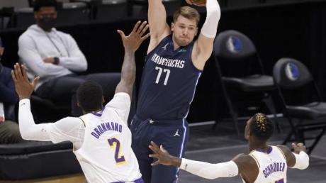 Mavericks-Star Luka Doncic (M) setzt sich gegen Dennis Schröder (r) und Andre Drummond von den Los Angeles Lakers durch.