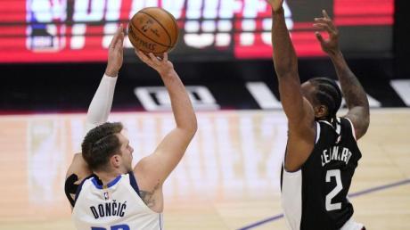 Luka Doncic (l) von den Dallas Mavericks wirft über Clippers-Starspieler Kawhi Leonard.