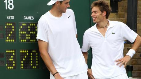 John Isner (l) und Nicolas Mahut posieren nach ihrem Rekordmatch 2010 neben der Anzeigetafel.