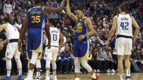 Kevin Durant (2.v.l) und Stephen Curry feiern den Sieg gegen die Dallas Mavericks. Foto: Richard W. Rodriguez/AP