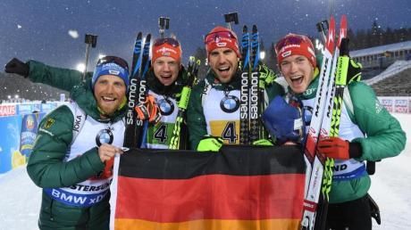 Erik Lesser (l-r-), Roman Rees, Arnd Peiffer und Benedikt Doll freuen sich mit einer deutschen Fahne über den zweiten Platz.